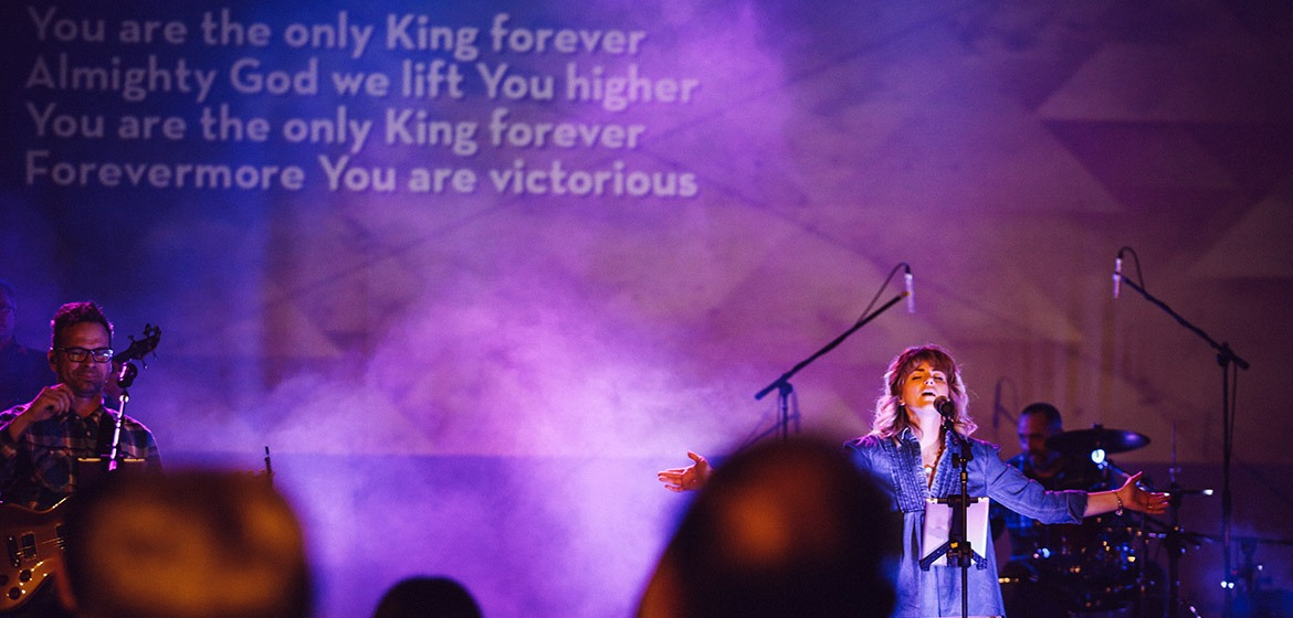 Female singer during time of worship with arms outstretched and words on screen